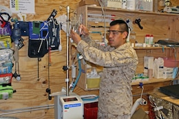 Seaman Victor Gonzalez, a hospitalman with Surgical Platoon, General Support Combat Logistics Company, Combat Logistics Regiment 2, explains how the rapid infuser operates, transfusing equal units of blood and plasma to the patient.  Gonzalez is part of the Shock Trauma Platoon located aboard Forward Operating Base Shukvani, Afghanistan.