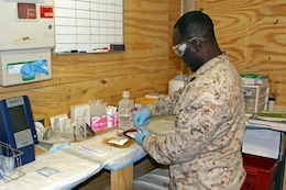 HM2 Keron Liverpool, a laboratory technician with Sugrical Platoon, Combat Logistics Regiment 2, demonstrates how he conducts a blood test. Liverpool works at the Role II medical facility located at Forward Operating Base Shukvani, which provides trauma care to troops operating in northern Helmand Province, Afghanistan.