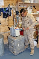 Seaman Victor Gonzalez, a hospitalman with Surgical Platoon, General Support Combat Logistics Company, Combat Logistics Regiment 2, sets up the rapid infuser he uses to conduct blood transfusions. Gonzalez works at the Role II medical facility located aboard Forward Operating Base Shukvani, Afghanistan.