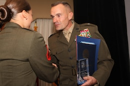 Cpl. Bilma J. Diaz, left, the NCO of the year at Weapons and Field Training Battalion, is presented an enlisted recognition award by Brig. Gen. Vincent A. Coglianese, right, the commanding general for Marine Corps Base Camp Pendleton and regional authority for five Marine Corps Installations in the southwestern United States.