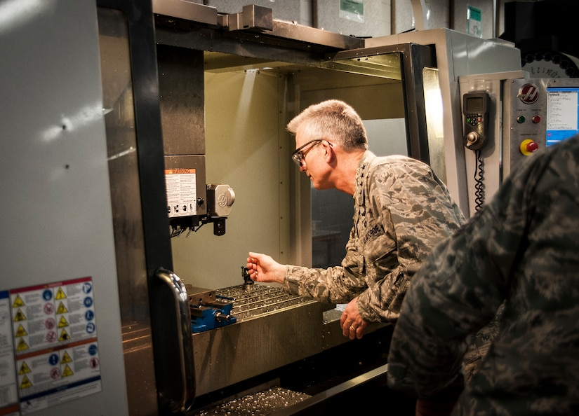 General Paul Selva, Air Mobility Command commander, reaches into a computer operated drill to look at a piece of metal fabricated at the 437th Aircraft Maintenance Squadron Metals Technology shop during a tour Feb. 13, 2013, at Joint Base Charleston – Air Base, S.C. Selva and Chief Master Sgt. Richard Kaiser, AMC command chief, arrived at JB Charleston, Feb. 13, 2013, for a three-day visit of extended tours of AMC units and installations JB Charleston. (U.S. Air Force photo/Senior Airman Dennis Sloan)