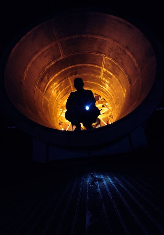 WHITEMAN AIR FORCE BASE, Mo. -- Senior Airman Kaitlyn Fawber, 509th Maintenance Squadron aerospace propulsion journeyman, shines a flash light on a test cell exhaust tube rivet, Feb. 13. The rivet maintains the sound-proofing in the cell. (U.S. Air Force photo/Staff Sgt. Nick Wilson) (Released)