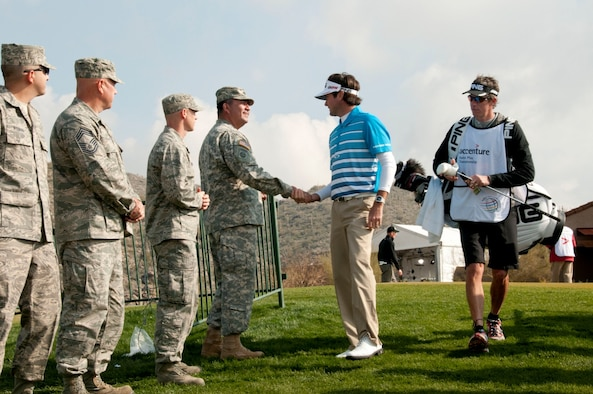 U.S. Army 1st Sgt. William Aragon, a soldier with the 285th Attack Reconnaissance Battalion, 'coins' PGA Tour golfer Bubba Watson as he makes his way to the first tee of the day at the Accenture Match Play Championship, held at the Golf Club at Dove Mountain in Marana, Ariz., Feb. 22.  Air and Army National Guardsmen from the 162nd Fighter Wing and the 285th Attack Reconnaissance Battalion in Tucson, Ariz. lined the walkway to the first hole to greet golfers before the beginning of play. (U.S. Air Force photo by Tech. Sgt. Hollie A. Hansen/Released)