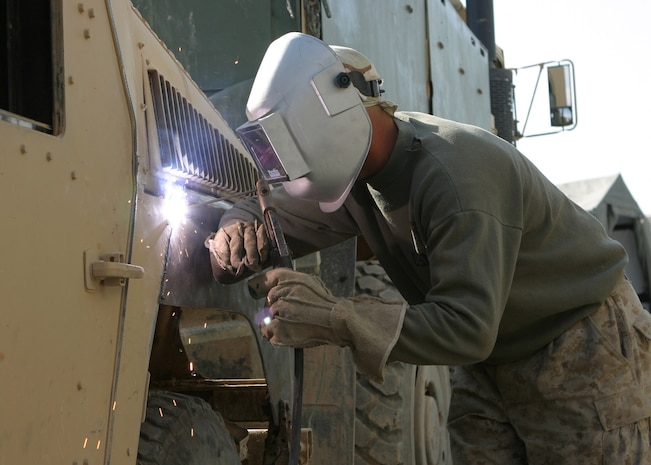 HADITHAH, Al Anbar, Iraq- 25 year old  Vermilion,Ohio native, Cpl. Jeffrey A. Thayer, a vehicle operator with 3/25, begins work on a HMMV needing more armor in the continuing effort to combat terrorism.