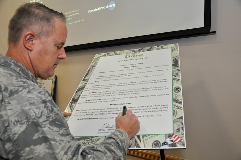 Col. Dan Dant, 460th Space Wing commander, signs the pledge starting Military Saves Week Feb. 26, 2013, at Bldg. 606 on Buckley Air Force Base, Colo.  The week is scheduled to include seminars and training on all varieties of financial matters. (U.S. Air Force photo by Staff Sgt. Nicholas Rau/Released)