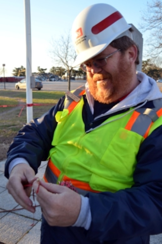 """Kevin Ewbank, Rock Island District park ranger, looks at an ornament made by students from a local school in Staten Island near Midland Beach before placing it back on the """"Tree of Hope,"""" Dec. 23. Ewbank is part of the Corps' Critical Incident Stress Management team trained to respond to a crisis and provide support to volunteers, family and friends."""