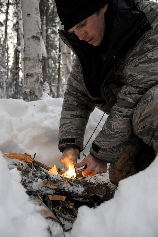U.S. Air Force 1st Lt. Isaac Landecker, 517th Air Lift Squadron C-17 pilot Joint Base Elmendorf Richardson, Alaska, ignites a fire during arctic survival training Feb. 20, 2013, Eielson Air Force Base, Alaska.  Landecker learned three different ways of starting fires:  split wood for wet weather, dry wood with dead branches, and deciduous fires when there is no useable pine wood.  (U.S. Air Force Photo/Airman 1st Class Peter Reft)