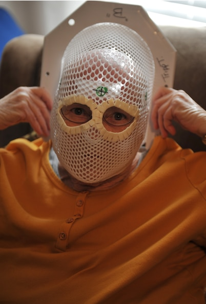 KNOB NOSTER, Mo. -- June Tripp, small cell cancer survivor, demonstrates the radiation mask she used during her radiation therapy, Feb. 19. June endured 15 days of radiation treatments to help shrink tumors and kill cancer cells. (U.S. Air Force photo/Heidi Hunt)