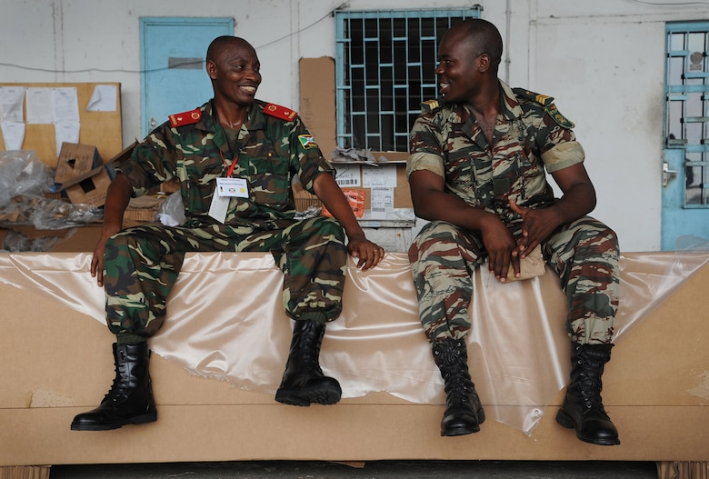 DOUALA, CAMEROON – African partner nation members share a quiet moment after building low cost low altitude bundles with U.S. Army parachute riggers assigned to the 5th Quartermaster Battalion Detachment, Kaiserslautern, Germany, at Douala Air Force Base, Douala, Cameroon, Feb. 21, 2013. Central Accord 2013 is a joint exercise in which U.S., Cameroon and neighboring Central African militaries partner to promote regional cooperation while and increasing aerial resupply and medical readiness capacity. (Photo by Master Sgt. Stan Parker, 621st CRW Public Affairs)
