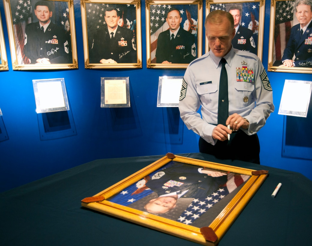 Chief Master Sgt. of the Air Force James Cody signs his portrait for the Enlisted Heritage Hall's Chiefs Wall at Maxwell Air Force Base during his visit here Feb. 26. (U.S. Air Force photo by Senior Airman Christopher Stoltz)