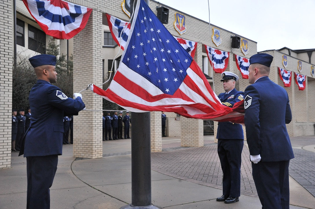 Airmen raise the flag in a revile ceremony during the 40th anniversary of the Air Force Senior NCO Academy. During the anniversary, Chief Master Sgt. of the Air Force James Cody served as the guest speaker for the celebration and spoke to the graduates about the strides the academy has made since its birth. (U.S. Air Force photo by Airman 1st Class William Blankenship)