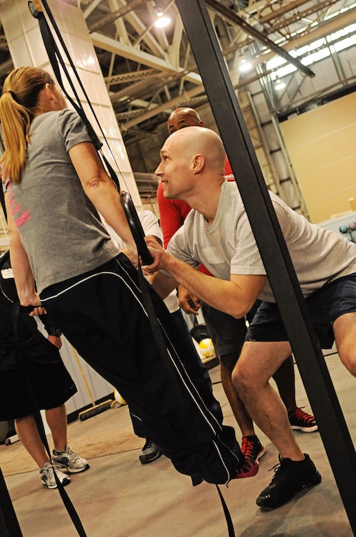 Members of the 102nd Intelligence Wing get trained on how to safely perform the exercises for the wing's new Tactical Fitness Program. The tactical fitness program brings a flexible, intense, team-based capability to the Air National Guard's most important weapon system, its Airmen, and is designed to better prepare them for AEF operations, as well as domestic operations. (National Guard photo by Tech. Sgt. Kerri Cole/Released)