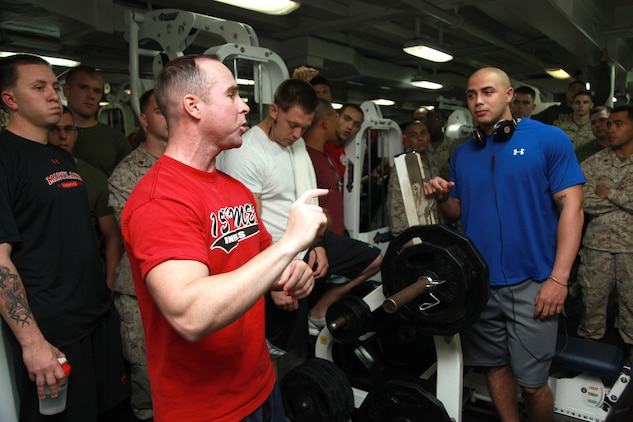 Religious Program Specialist 1st Class Edward S. DeBaun, Command Element, 15th Marine Expeditionary Unit, explains the rules of the Bench Press Competition in the gym of the USS Peleliu, Dec. 29. The challenge was the seventh competition in the Campbell Cup, a bi-monthly challenge that pits teams within the 15th MEU and Peleliu Amphibious Ready Group against each other. The goal was for teams of up five Marines or sailors to do as many bench presses as possible per team member. The 15th MEU is deployed as part of the Peleliu ARG as a U.S. Central Command theater reserve force, providing support for maritime security operations and theater security cooperation efforts in the U.S. 5th Fleet area of responsibility. DeBaun, 35, is from Copperopolis, Calif.