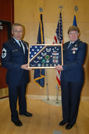 Chief Master Sgt. Steve Schiele presents a shadow box to Lt. Col. Cecilia Nackowski during her retirement ceremony at the Utah Air National Guard Base Dec. 2. Nackowski formally retired after 35 years of military service.(U.S. Air Force photo by Capt. Wayne Lee)(RELEASED)