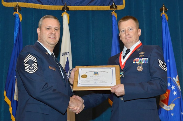 Master Sgt. James E. Pepin awarded the Noncommissioned Officer Academy's distinguished graduate award to Utah Air National Guard member Tech. Sgt. Harry Grow at McGhee Tyson Air National Guard Base, Tenn. on Dec. 12. The distinguished graduate award is presented to students in the top ten percent of the class. It is based on objective and performance evaluations, demonstrated leadership, and performance as a team player. (Air Force photo by Master Sgt. Kurt Skoglund/Released)