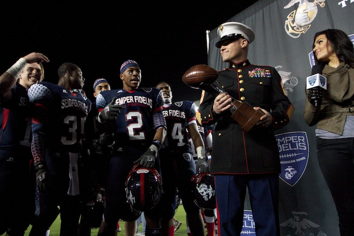 Sgt. Maj. Micheal Barrett, Sergeant Major of the Marine Corps, presents the Semper Fidelis All-American Bowl trophy to the East Coast team for their 17-14 win against the West on Jan. 4, 2013. The Semper Fidelis Bowl is unique because it brings together some of the nations top high school student athletes who excel not only on the field but in the classroom and in their communities as well.
