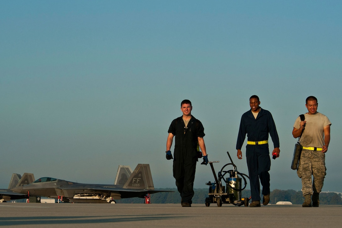 (From left) Airman 1st Class Travis Miron, Senior Airman Justin Stith and Airman 1st Class San You, all F-22 Raptor crew chiefs, walk off the Joint Base Langley-Eustis flightline after eight successful F-22 takeoffs. (U.S. Air Force photo/Tech. Sgt. Bennie J. Davis III)