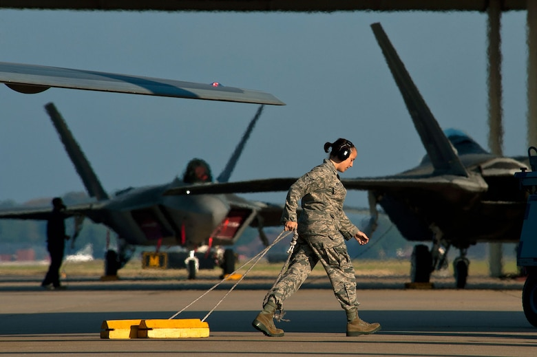 Airman 1st Class Meaghan Mueller, a crew chief, pulls the chocks from beneath an F-22 Raptor on the Joint Base Langley-Eustis flightline before a training mission. (U.S. Air Force photo/Tech. Sgt. Bennie J. Davis III)