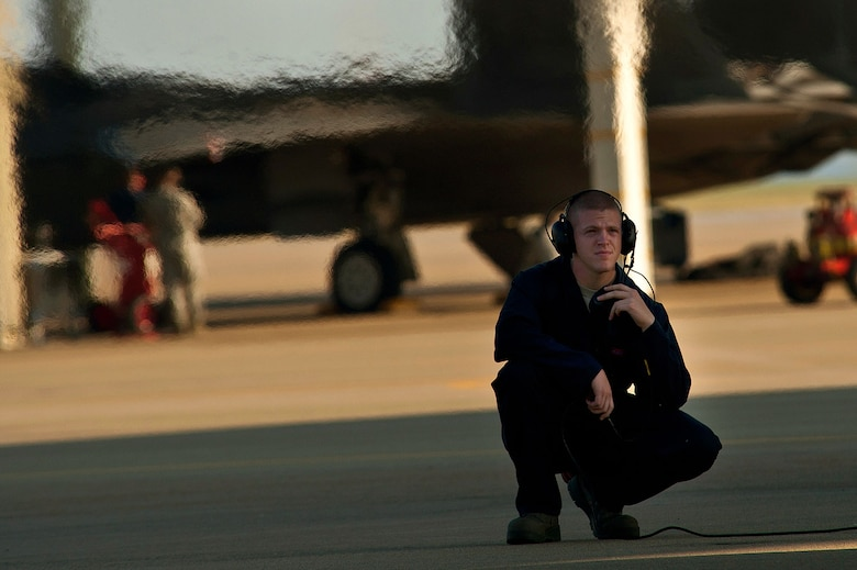 Airman 1st Class Benjamin Speer, an F-22 crew chief, watches over an aircraft and communicates with a pilot during a preflight inspection before a training mission. (U.S. Air Force photo/Tech. Sgt. Bennie J. Davis III)