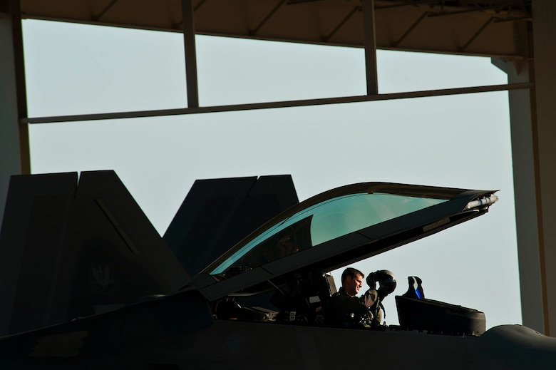 Lt. Col. David Lopez inspects his helmet inside the cockpit of an F-22 Raptor while preparing for takeoff. Lopez is the deputy director of operations for the 1st Operations Support Squadron. (U.S. Air Force photo/Tech. Sgt. Bennie J. Davis III)