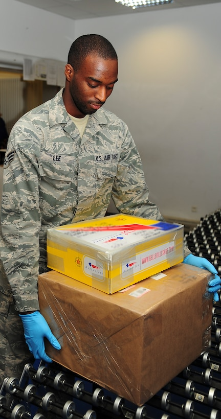 Senior Airman Jonathan Lee, 86th Communication Squadron postal specialist, brings mail to the service window at the Northside Post Office on Ramstein Air Base, Germany, Dec. 17, 2012. The post office receives its highest customer traffic during the holiday season. (U.S. Air Force photo/Airman 1st Class Jordan Castelan)