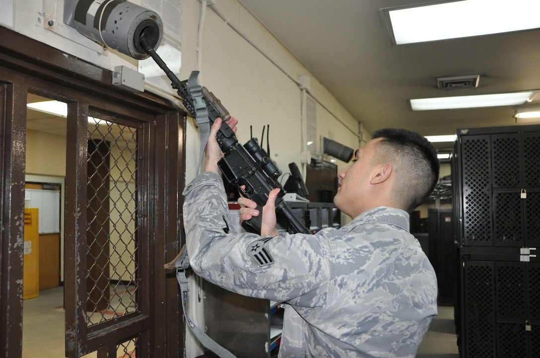 Senior Airman Andrew Smalley, 51st Security Forces armory assistant NCO in charge, inspects the barrel of an M-4 carbine for cleanliness Jan. 4, 2013. After each shift, weapons must be cleared by the security forces Airmen, and then turned into the armory for security until the individual needs it again for duty. (U.S. Air Force photo/Senior Airman Kristina Overton)