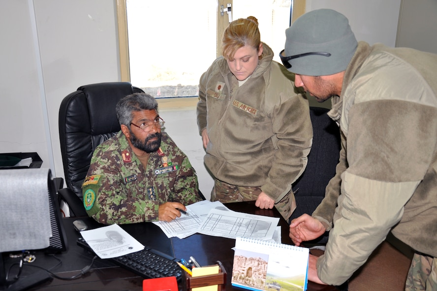 Maj. Deanna Daly, staff judge advocate for the 451st Air Expeditionary Wing at Kandahar Airfield, advises Afghan Col. Saaid Ahmad, her counterpart at the Kandahar Air Wing, an Afghan Air Force unit based at KAF. Due to the language barrier, the two communicate using an interpreter (right). Daly and her paralegal, Tech. Sgt. Terry Beasley, have been advising the KAW legal office on issues such as military justice and non-judicial punishment. (Photo by Capt. Tristan Hinderliter/U.S. Air Force)