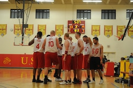 Marine Corps Intelligence Activities intramural basketball team huddles together during a timeout at the first game of the season at Barber Physical Fitness Center on Monday. MCIA faced off against Enlistment Incentive Program's intramural basketball team for the 42-22 win.