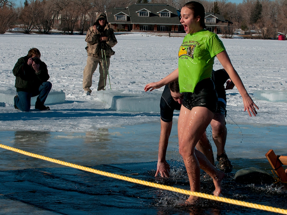 Participants in the Matthew S. Schwartz Memorial Polar Plunge scamper out of the 27-degree water of Sloan Lake and head for the warming tent, Jan. 5, 2012, at Frontier Park in Cheyenne, Wyo. The event was a fundraiser for the Wounded EOD Warrior Foundation held on the one-year anniversary of U.S. Air Force Tech. Sgt. Matthew Schwartz's death in Afghanistan. Schwartz was a member of the 90th Civil Engineer Squadron on F.E. Warren AFB. (U.S. Air Force photo by R.J. Oriez/Released)