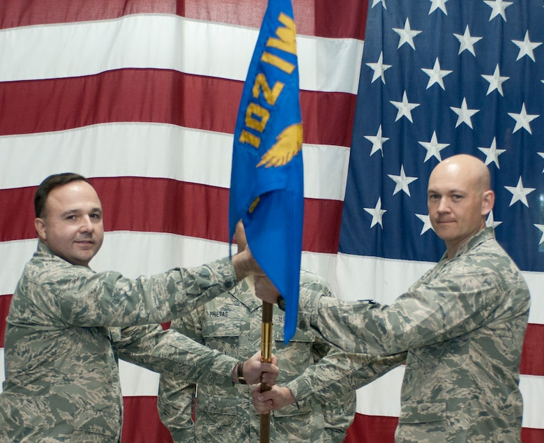 Lt. Col. Christopher Hamilton, 102nd Mission Support Group commander, passes the 102nd Security Forces Squadron flag to Capt. Christian Leighton during an assumption of command ceremony on Otis Air National Guard Base Dec. 2. Leighton assumed command of the 102nd Security Forces Squadron, which he was once a member of as an enlisted Airman. (Air National Guard photo by Senior Airman Patrick McKenna/Released)