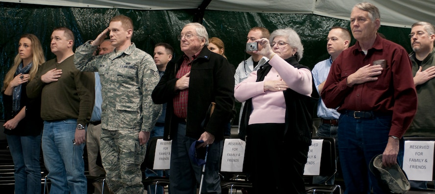 Family and friends of Capt. Christian Leighton stand as the national anthem is played at the beginning of Leighton's assumption of command ceremony on Otis Air National Guard Base Dec. 2. Leighton assumed command of the 102nd Security Forces Squadron, which he was once a member of as an enlisted Airman. (Air National Guard photo by Senior Airman Patrick McKenna/Released)