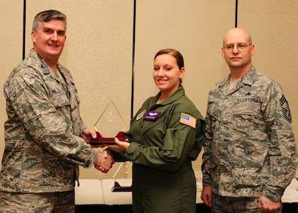 Col. Al Miller, 437th Airlift Wing vice commander, and Chief Master Sgt. Gerard Komen, 437th Maintenance Operations Squadron superintendent, present the Diamond Sharp award to Senior Airman Brandi Lopez, 15th Airlift Squadron loadmaster, Jan. 8, 2013, at Joint Base Charleston - Air Base, S.C. The Diamond Sharp awards recognize individuals in a unit who stand out to their first sergeant. (U.S. Air Force photo/ Airman 1st Class Chacarra Walker)