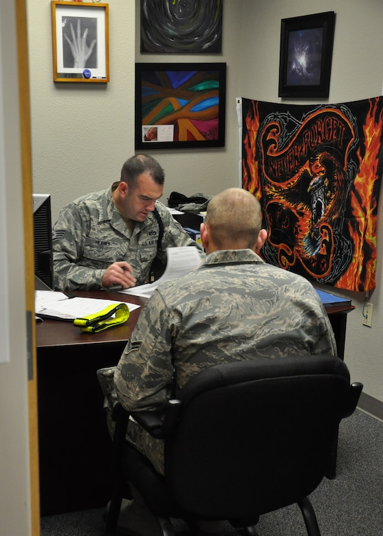 GOODFELLOW AIR FORCE BASE, Texas - Staff Sgt. Barak Heaney, 316th Training Squadron military training instructor, reviews Airman 1st Class Michael Litherland's, 316th Training Squadron student, final out processing checklist in Heaney's office at Building 3139 here, Dec. 20. This is one of the last steps Litherland needed to complete before moving on to his next duty station. (U.S. Air Force photo/ Airman 1st Class Joshua Edwards)