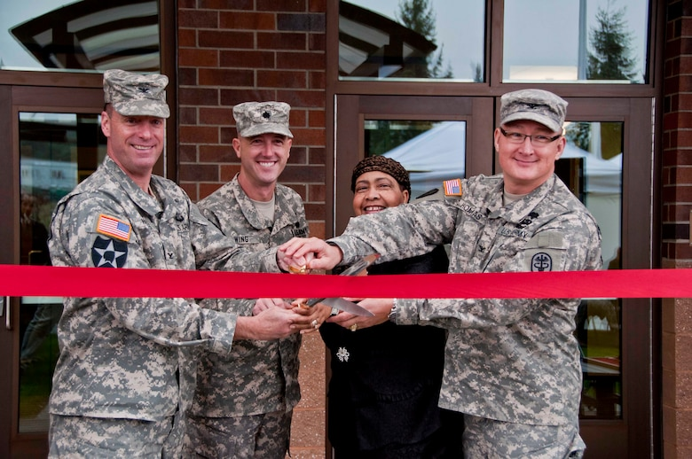From left, Col. H. Charles Hodges, Joint Base Lewis-McChord commanders; Lt. COl. Jason Wing, Warrior Transition Battalion commander; Jacqueline Seabrook, Soldier and Family Assistance Center director; and Col. Dallas Homas, Madigan Healthcare System commander; cut the ribbon during the Installation Management Command's ceremony for the Soldier and Family Assistance Center and Open House for the Warrior Transistion Battalion Headquarters held Jan. 7 at Joint Base Lewis McChord.  The building was a U.S. Army Corps of Engineers, Seattle District, military construction project and was built by Doyon Government Group.