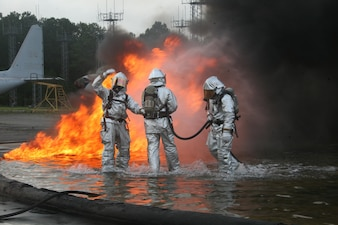 Marines with air station Aircraft Rescue and Firefighting works on putting out a fire in a pit of water and jet fuel during a fuel fire training.