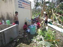 A community devastated by Typhoon Bopha uses water funneled from a mountain for bathing and washing laundry here Dec. 10. The Armed Forces of the Philippines and the U.S. Marine Corps Forces, Pacific Experimentation Center joined to gather operational feedback on water purification systems and while providing relief efforts to typhoon victims.