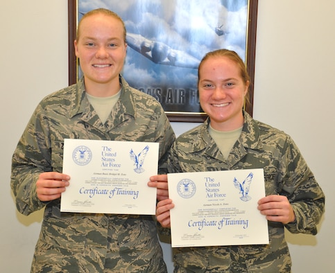 Airman Basic Bridgit Zens and Airman Nicole Zens, 335th Training Squadron students , display their certificates of completion after finishing the avionics fundamental course Dec. 18 at Keesler  Air Force Base, Miss. The two sisters entered basic training together and were in the same class for avionics training here.  (U.S. Air Force photo by Staff Sgt. Eric Summers Jr.)