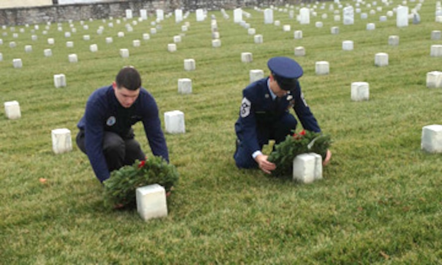 Senior Airman Jacob Bixler and Command Chief Master Sgt. Ronald Glazer place wreaths on the graves of veterans at the Winchester National Cemetary in Winchester, Va.,  as part of the Wreaths Across America event
