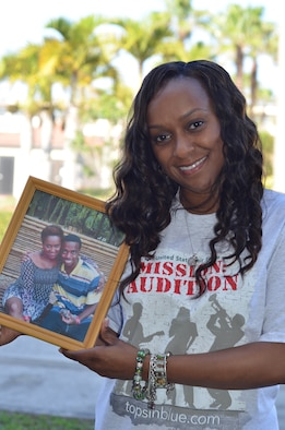 Air Force Reservist, Tech. Sgt. Altrameise Myers, information management craftsman, 920th Rescue Wing, Patrick Air Force Base, Fla., poses with a photo of her late son AJ who passed away at 17 years old, Sept. 30, 2012. Myers' grief helped to melt away her stage fright which led to an invite to audition for the Air Force's highly coveted Air Force Tops in Blue entertainment troupe. (U.S. Air Force photo/Capt. Cathleen Snow)