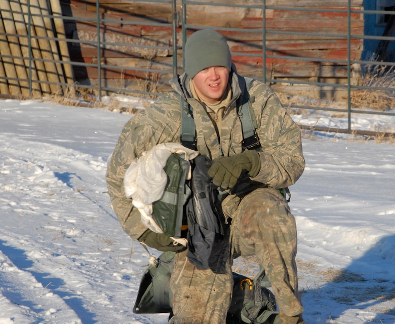 SIOUX FALLS, S.D.- Staff Sgt. Bo Martz, 175 Fighter Squadron Aircrew Flight Equipment technician, kneels in the snow with a paracute while instructing the Survival Evasion Resistance and Escape refresher training during combat survival training near Joe Foss Field, S.D. Jan. 6.  (National Guard photo by Senior Airman Amanda Bradshaw)(Released)