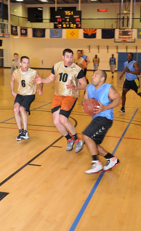 Tech. Sgt Ivan Vargas, right, Joint Special Operations Air Component joint operations specialist, evades Staff Sgt. Andrew Valence, 351st Air Refueling Squadron boom operator, and Staff Sgt. Everett Marshall, 351st ARS boom operator, during an intramural basketball game between the 100th Operations Group and the 352nd Special Operations Support Squadron Jan. 10, 2013, at the Hardstand Fitness Center on RAF Mildenhall, England. The 352nd SOSS were victorious over the 100th OG with a score of 55-41. (U.S. Air Force photo by Airman 1st Class Dillon Johnston/Released)