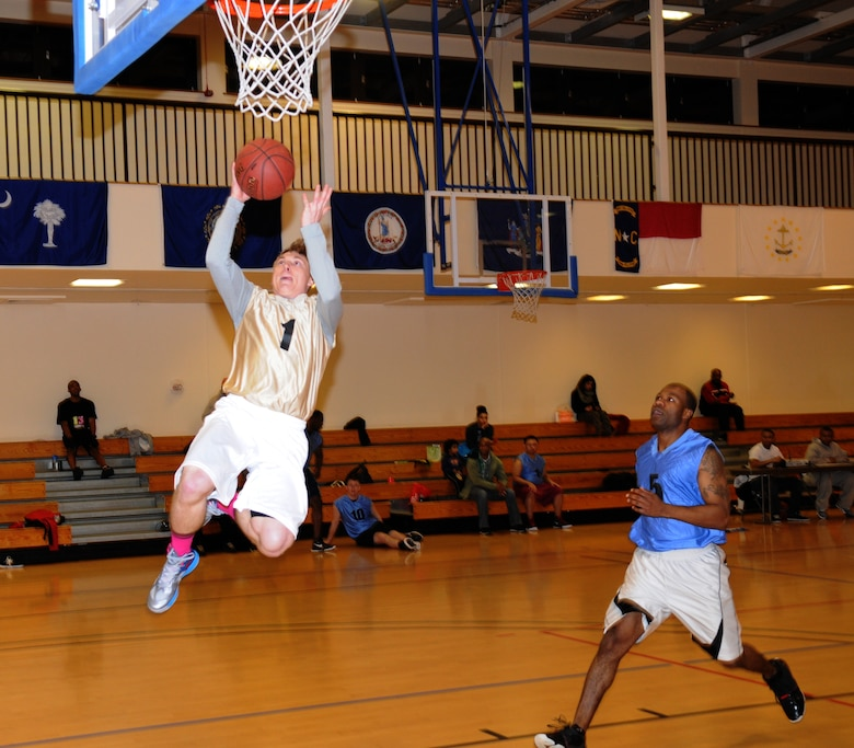 Airman 1st Class Caleb Johnson, left, 100th Operations Support Squadron airfield manager, jumps for a layup while Tech. Sgt. Richard Brown, 352nd Special Operations Support Squadron NCO in charge of intelligence operations, gives chase during an intramural basketball game between the 100th Operations Group and the 352nd Special Operations Support Squadron Jan. 10, 2013, at the Hardstand Fitness Center on RAF Mildenhall, England. The 352nd SOSS were victorious over the 100th OG with a score of 55-41. (U.S. Air Force photo by Airman 1st Class Dillon Johnston/Released)
