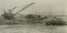 A crane and drag line, which is attached to a dredging bucket, is at work in a sump area of the Livingstone Channel. On the right side of this photo, taken in 1933, is a scow where dredged materials were placed and then pumped to the opposite side of the coffer dam.