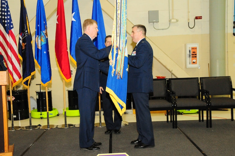 Major General Verle Johnston, the commander of the New York Air National Guard hands the 107th Airlift Wing's flag to Col. John Higgins as he assumes command at the Niagara Falls Reserve Station on Jan. 12, 2013 (Air National Guard Photo/Senior Master Sgt. Ray Lloyd)