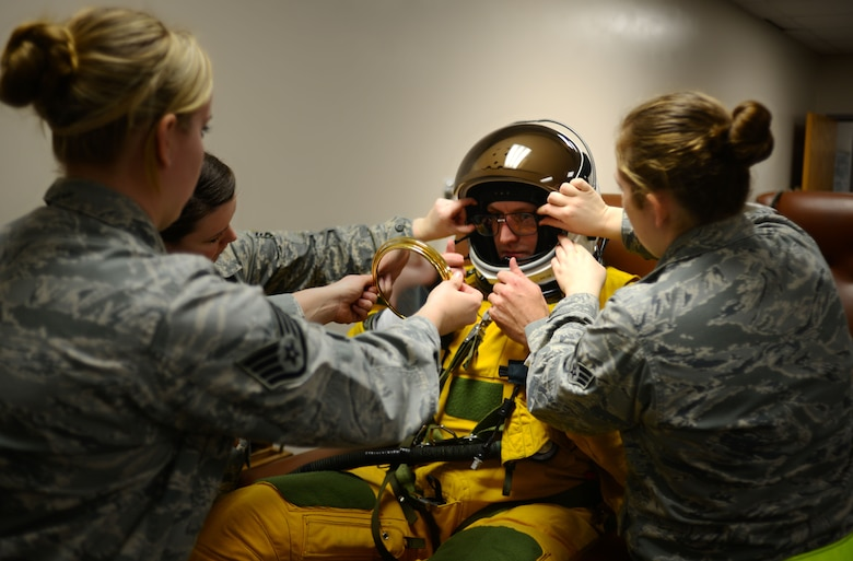 Staff Sgt. Vanessa Jordan (left ) 9th Physiological Support Squadron launch and recovery technician, uses a mirror to confirm placement of U-2 pilot Capt. Travis' specialized glasses within his helmet as Staff Sgt. Heather Doyle and Senior Airman Meghan Mattingly assist Jan. 8, 2013, at Beale Air Force Base, Calif. Dawning of the highly specialized full pressure suit requires a team of physiological support personnel. The squadron is the only one of its kind in the Department of Defense, with the responsibility of ensuring survivability of the nation's team of U-2 pilots. (U.S. Air Force photo by Airman 1st Class Drew Buchanan/Released)