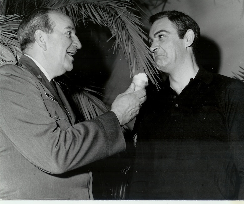 """Retired Lieutenant Colonel Charles Russhon, military advisor to the James Bond films in the '60s and '70s, feigns shoving a vanilla ice cream cone in Sean Connery's face during the production of """"Thunderball."""" Russhon and Connery became friends on set. The vanilla ice cream cone had special significance to Russhon, who inspired the """"Charlie Vanilla"""" character, an ice cream loving mister fix-it, in friend and esteemed American cartoonist Milton Caniff's comic strip """"Steve Canyon."""" (Photo courtesy of Christian Russhon)"""