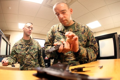 U.S. Marine Capt. Steve Draper, a logistics advisor with the Operation Onward Liberty Security Cooperation Team, disassembles a Tokarev semi-automatic pistol during the foreign weapons handling portion of the team's pre-deployment training prior to supporting Operation Onward Liberty. Draper is stationed at Headquarters Battalion, Third Marine Division in Okinawa Japan and is a native of West Milton, Ohio.