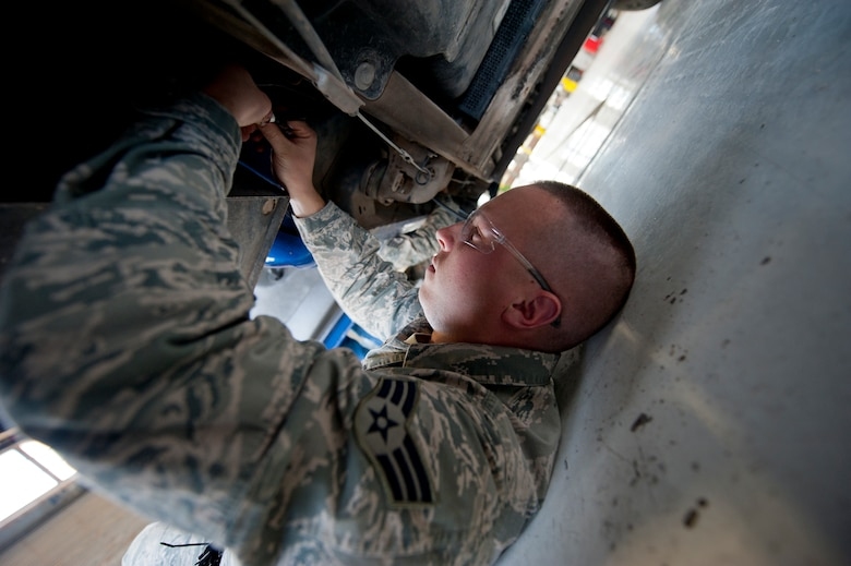"""Senior Airman Matthew Aucutt, a 49th Logistics Readiness Squadron vehicle maintainer, installs an Automotive Informational Module (version 2.4), better known as """"AIM2,"""" at Holloman Air Force Base, N.M., Dec. 18. He, another Airman, and two contractors have been dedicated to installing AIM2 systems here since November 2012. Ninety percent of the vehicles here are upgraded, and the project will be complete by the end of January. (U.S. Air Force photo by Staff Sgt. Carolyn Herrick/released)"""