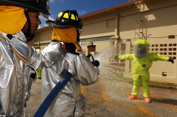 Airmen from the 36th Civil Engineer Squadron decontaminate a 36th Medical Operations Squadron bioenvironmental engineering technician before he exits the cordon of a hazardous material investigation during an operational readiness exercise Andersen Air Force Base, Guam, Jan. 14, 2013. (U.S. Air Force photo by Senior Airman Carlin Leslie/Released)