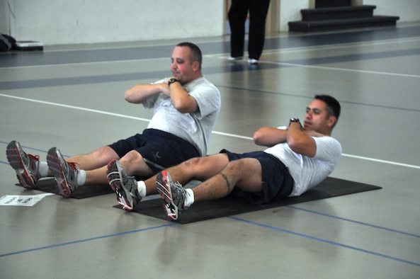 GOODFELLOW AIR FORCE BASE, Texas – Staff Sgt. Robert Prince, 17th Training Support Squadron unit training manager, and Master Sgt. Gregorio Escamilla, 17th Training Support Squadron flight chief, participate in one of the circuit training stations at the Carswell Field House here, Jan. 14. This station and others were incorporated into the circuit training to focus on the abdominal sections. (U.S Air Force photo/ Airman 1st Class Joshua Edwards)